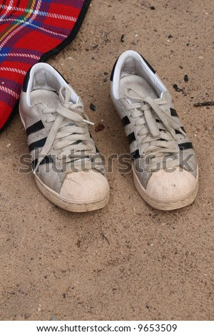 Old white sneakers on the sand - stock photo