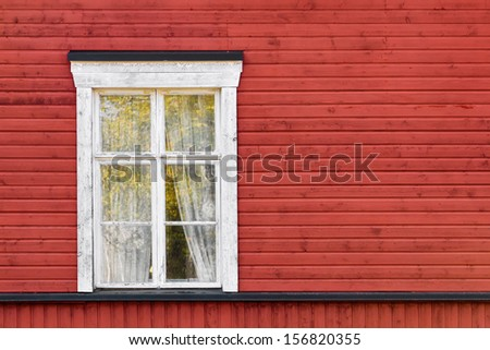 Old white window on red wooden wall