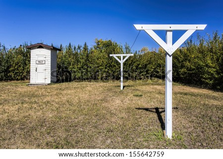 Old white wooden clothes lines by an outhouse - stock photo