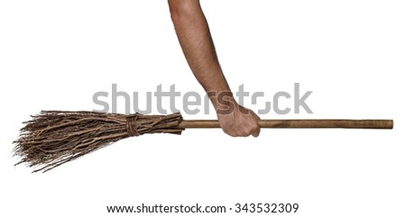 Old wicked witches broomstick being held in clenched right hand - stock photo
