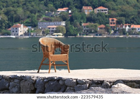 old wicker rattan chair on the seafront the Bay of Kotor. Montenegro  - stock photo