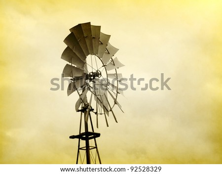 Old wind driven water pump on a farm - stock photo