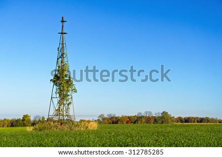 Old Wind Tower in Disrepair in Rural  Hay Field - stock photo