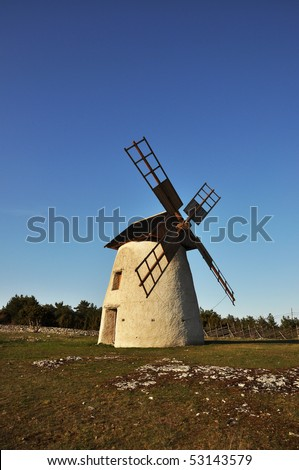 Old windmill against blue sky. - stock photo