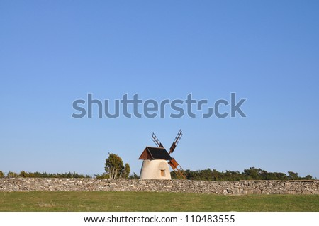 Old windmill by old stone wall in the country. - stock photo