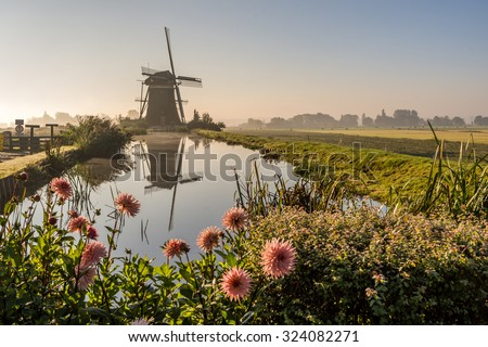 Old windmill in foggy Netherlands countryside landscape (Leidschendam, South Holland)  - stock photo