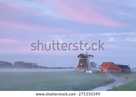old windmill in sunrise fog by river, Netherlands - stock photo
