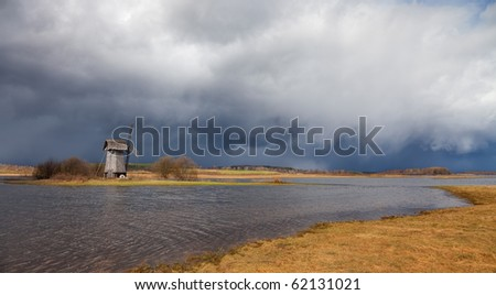 old windmill on field near river - stock photo