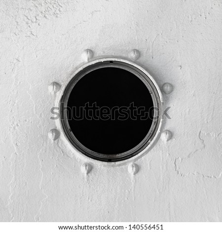 Old window at the gray wall of the vessel - stock photo