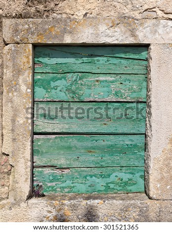 Old window boarded up with wooden planks. - stock photo