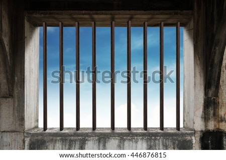 Old window frame with iron bar in jail, and blue sky - stock photo
