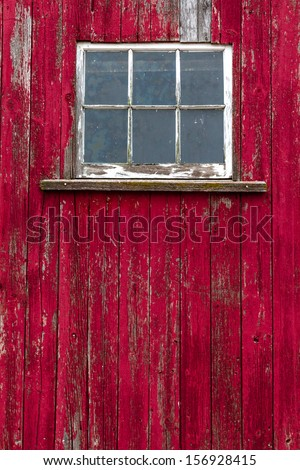 Old window on abandoned red barn with textured old split wood - stock photo