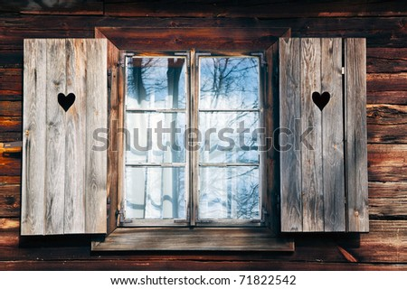 Old window shutters in wooden wall. Nowogrod Heritage Park, Masuria, Poland - stock photo