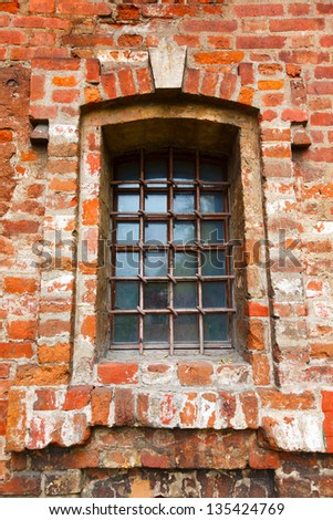 Old window with bars in a red brick - stock photo