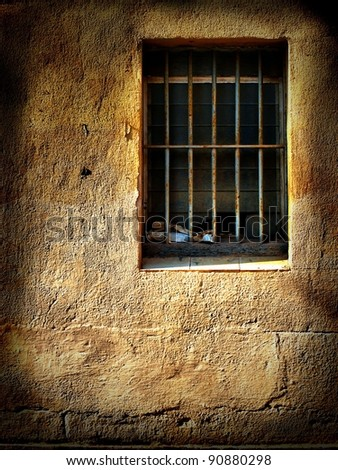 Old window with bars on grungy wall - stock photo