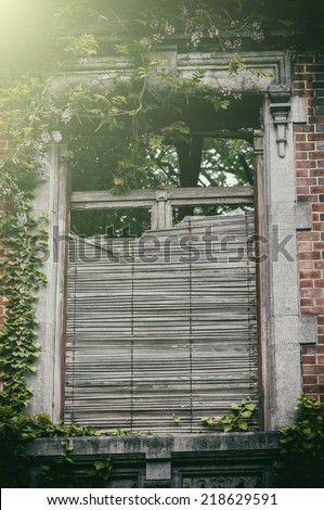 Old window with broken wooden shutters - stock photo