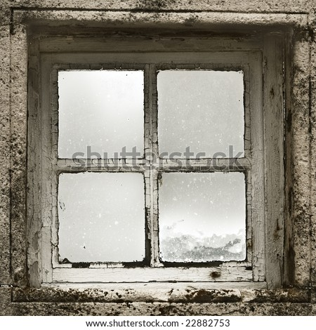 Old window with cracked paint from the inside looking out into the cold winter. - stock photo