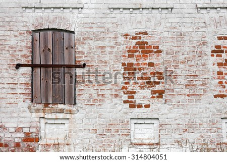 Old window with creative metal bars on the white stone wall - stock photo