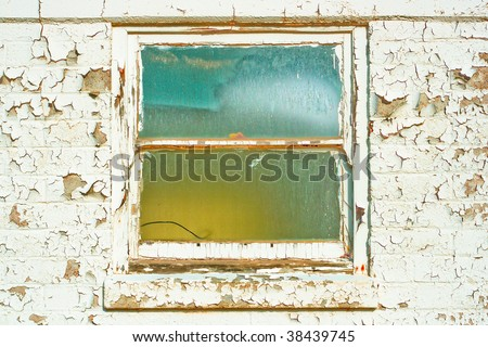Old window with surrounded by wall with peeling paint.