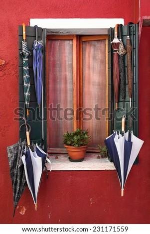 Old window with umbrellas. Burano. Venice. Italy - stock photo