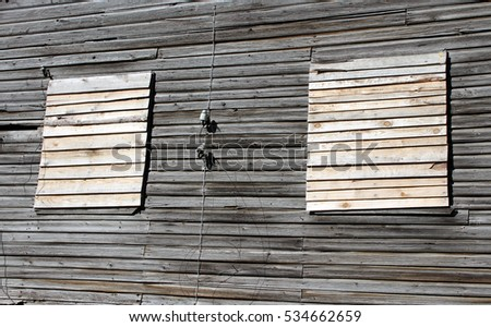 Old windows with closed wooden planks