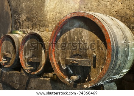 Old wine barrels in a wine cellar with mold and cobwebs - stock photo