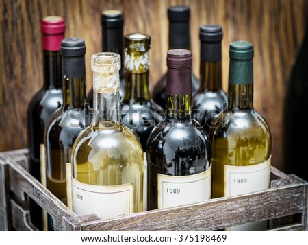 Old wine bottles in a wooden crate.  - stock photo