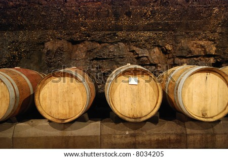 Old wine cave with wooden barrels - stock photo