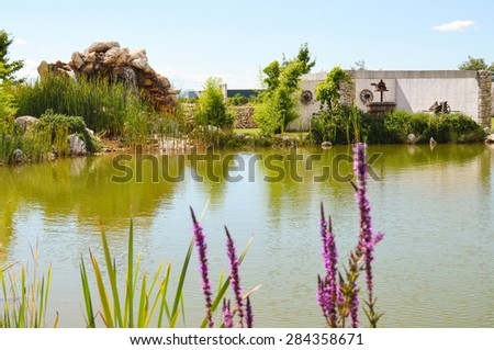Old winery by the calm pond - stock photo