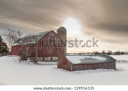 Old winter barn on snow covered farm field in northern Ontario. - stock photo