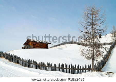Old winter wood cottage with fence in Dolomiti Alps, Ortisei, italy. - stock photo