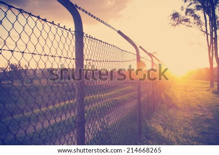 Old wire fence with the sun streaming alongside it - stock photo