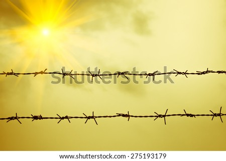 Old wire fence with the sunbeam and yellow color background - stock photo