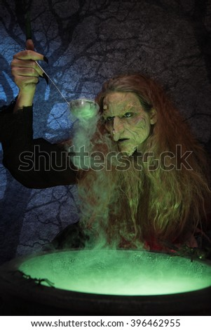 Old witch brewing magical potion - stock photo