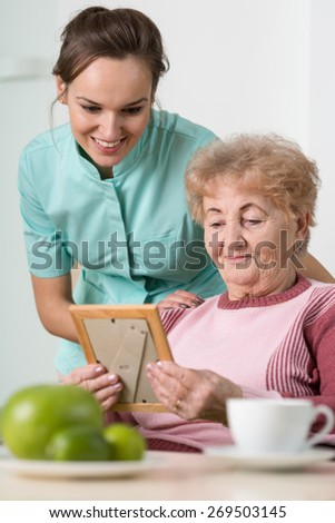Old woman and her nurse looking at a sentimental photo