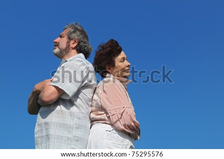 old woman and man standing back to back, crossed hands