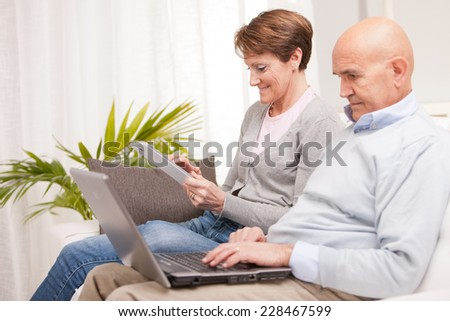 old woman and old men happy together because they love each other in a living room on a sofa