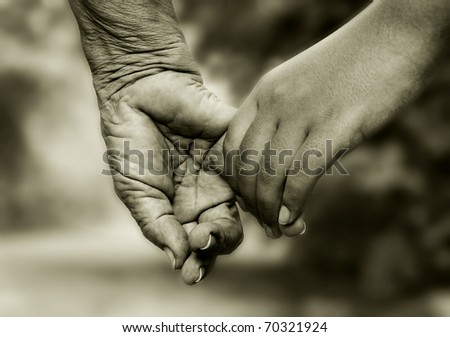 Old woman and young girl holding hands together - stock photo
