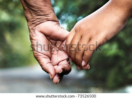 Old woman and young girl holding hands together