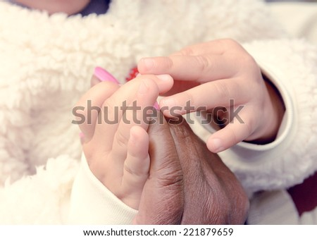 Old woman and young girl holding hands together,selective focus  - stock photo