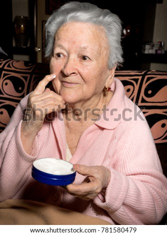 Old woman applying anti-aging cream at home