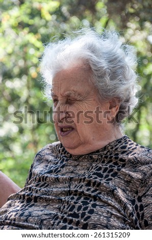 old woman at park in spring - stock photo