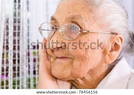 Old woman at the window, dreaming the past - stock photo