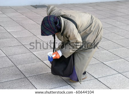 Old woman begging on the street - stock photo