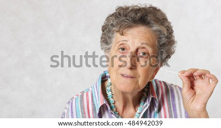 Old woman between 70 and 80 years old is cleaning her years with cotton swabs