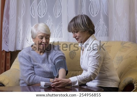 Old woman checking blood pressure - stock photo
