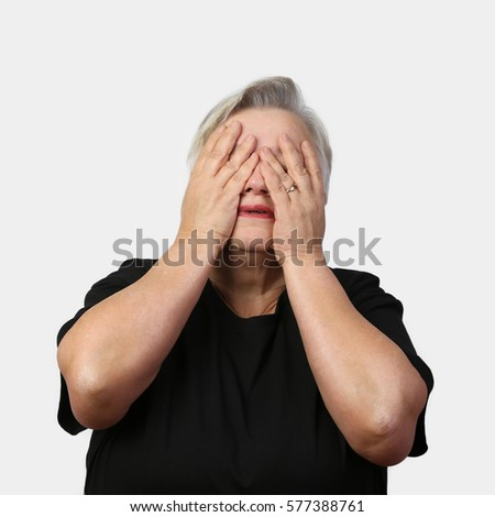 Old woman closed eyes with hands on gray background - hopelessness and despair