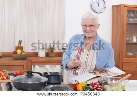 Old woman cooking - stock photo