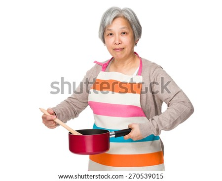 Old woman cooking food - stock photo