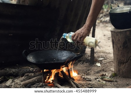 Old woman cooking in Thai kitchen,pouring oil into the pan.